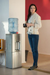 37053088 - young woman using water dispenser at office